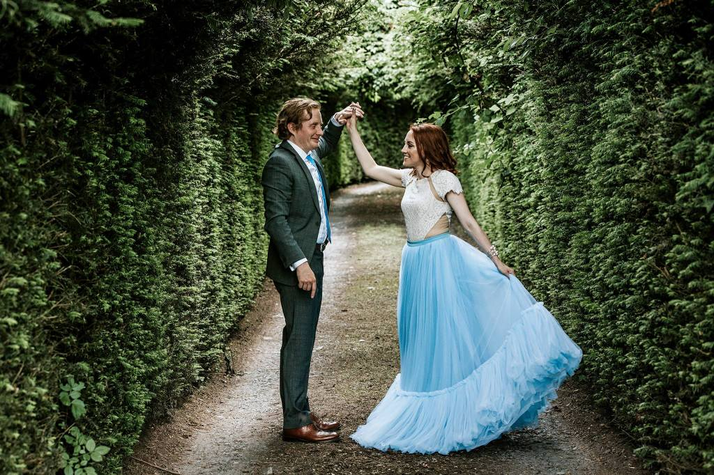 Alex twirls Clare in a blue wedding dress, in a picturesque corridor of greenery.